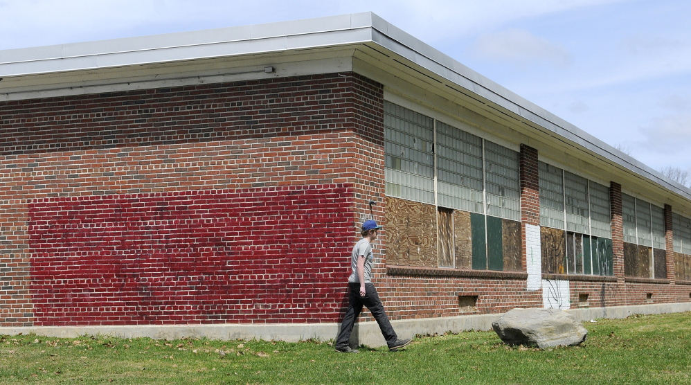 STURDY CONSTRUCTION: Tyler Lessard, 15, walks Tuesday around the former Hodgkins Middle School in Augusta to the nature trails behind it.