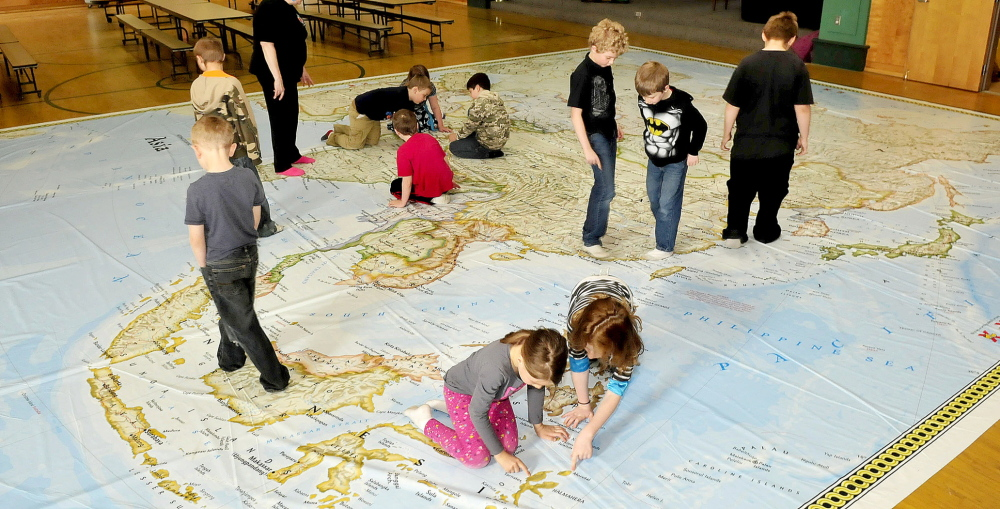 LOST IN SPACE: Students at Garrett Schenck School in Anson explore a giant map of Asia courtesy of the Maine Geographic Alliance on Tuesday.
