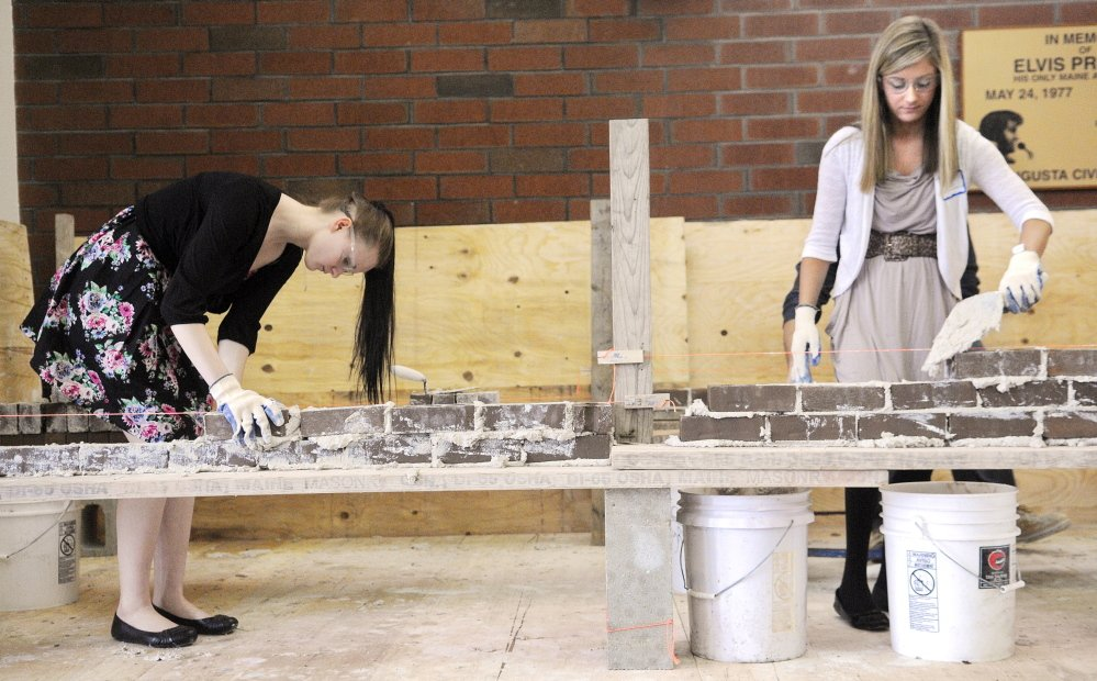 GETTING AWAY WITH MORTAR: Waterville High School student Destiny Petit, left, and Madison Area Memorial High School student Gretchen Miller assemble a brick wall Wednesday during the annual Jobs for Maine's Graduates Career Development Conference in Augusta. The daylong conference introduced JMG students to a variety skills and employers, including the Maine Masonry Co.