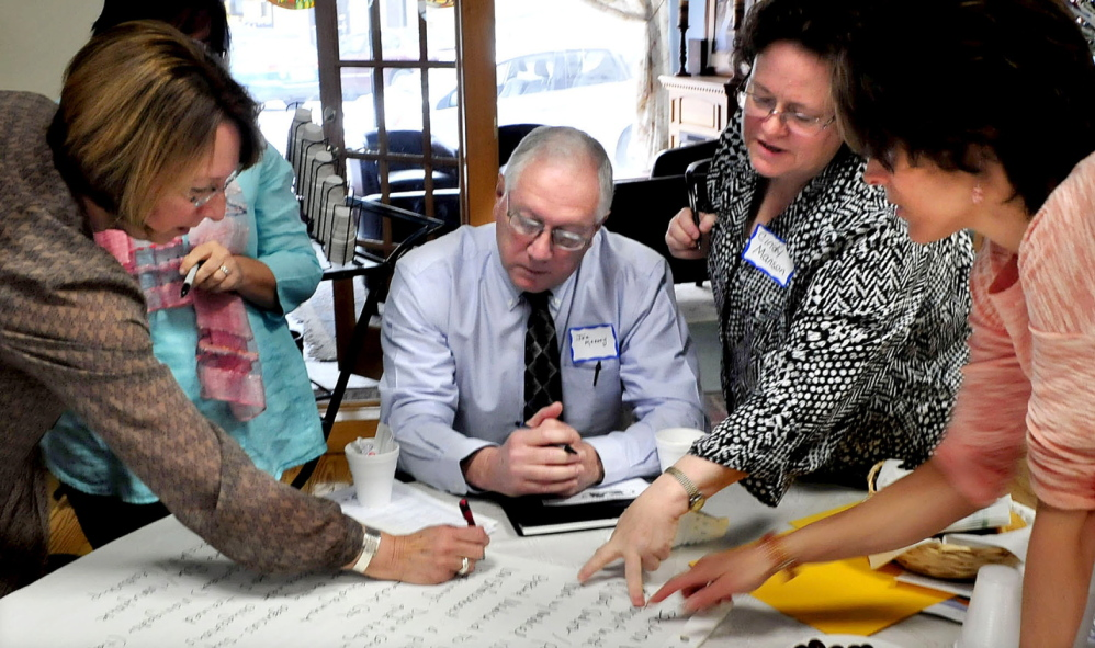 PROBLEM SOLVERS: A forum involving multiple agencies was held in Waterville to deal with the problem of youth homelessness on Wednesday. Ann Bouchard, left, Waterville Police Chief Joseph Massey, Cindy Manson and Elizabeth Hartford consult with their selections of issues during a group strategy session.