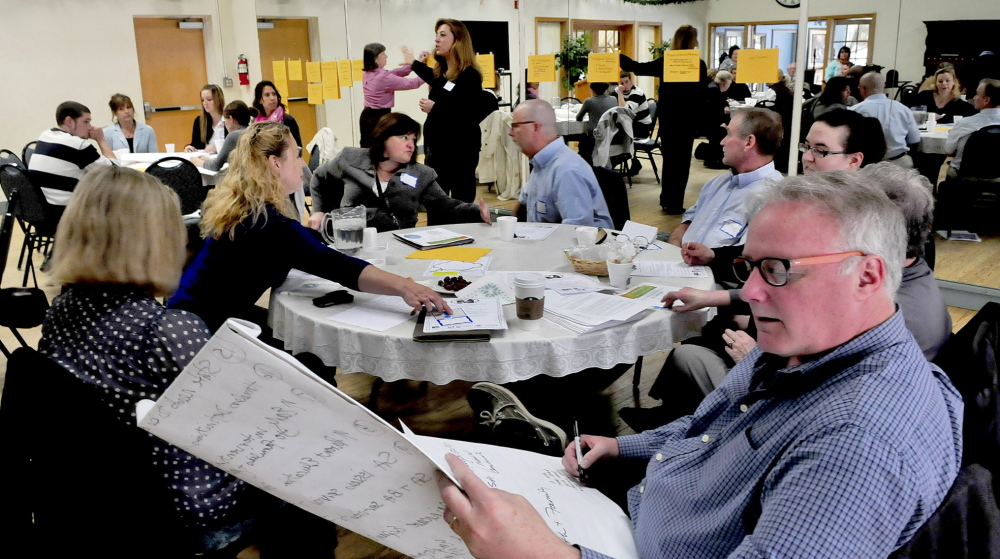SOLUTIONS: Multiple agencies, including a group from Kennebec Behavior Services, in foreground, met on Wednesday to discuss solutions to youth homelessness. Ideas for dealing with the problem were posted on a wall, in the background, and later prioritized by the groups.