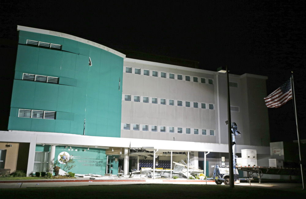 Debris from an explosion at the Escambia County Jail is scattered at the entrance to the facility, Thursday, May 1, 2014, in Pensacola, Fla. Two inmates were killed and more than 100 others injured in the explosion according to an Escambia County spokeswoman.