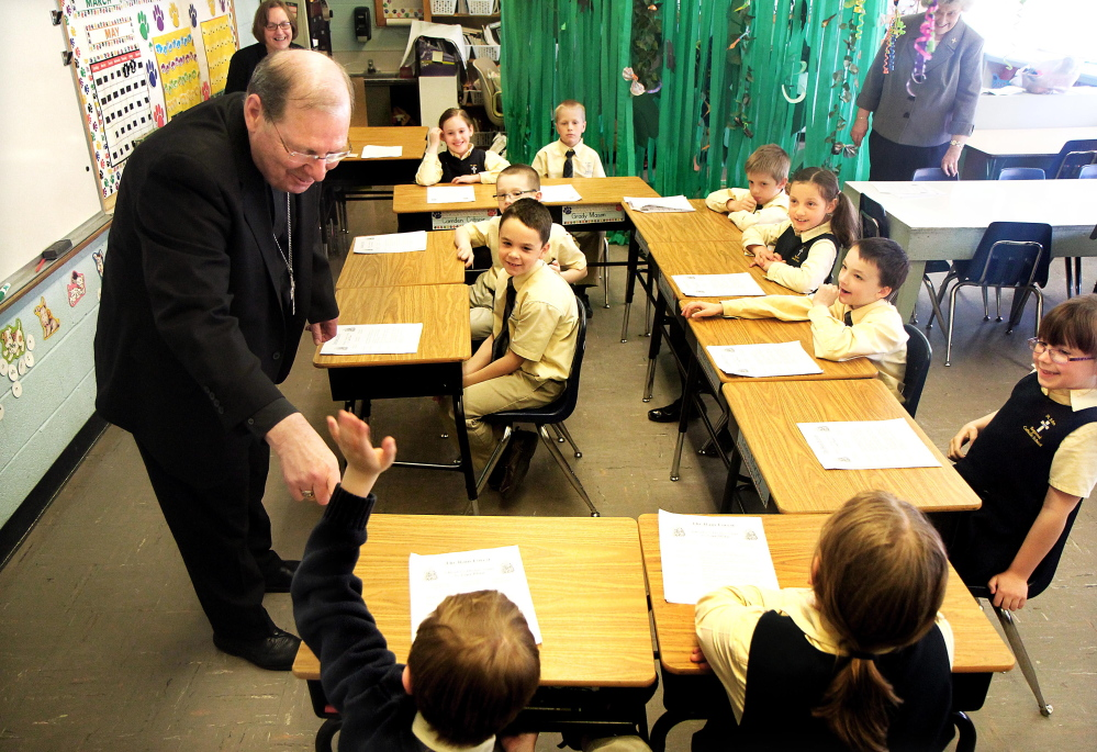 ANSWERING A QUESTION: Bishop Robert Deeley of the Roman Catholic Diocese of Portland responds to a question by Nolan Kelley, lower left, while visiting with students in Lucille Nassar's second grade class at St. John Regional Catholic School in Winslow on Friday. Deeley said he has traveled 9,000 miles in the last 10 weeks visiting parishioners across the state.
