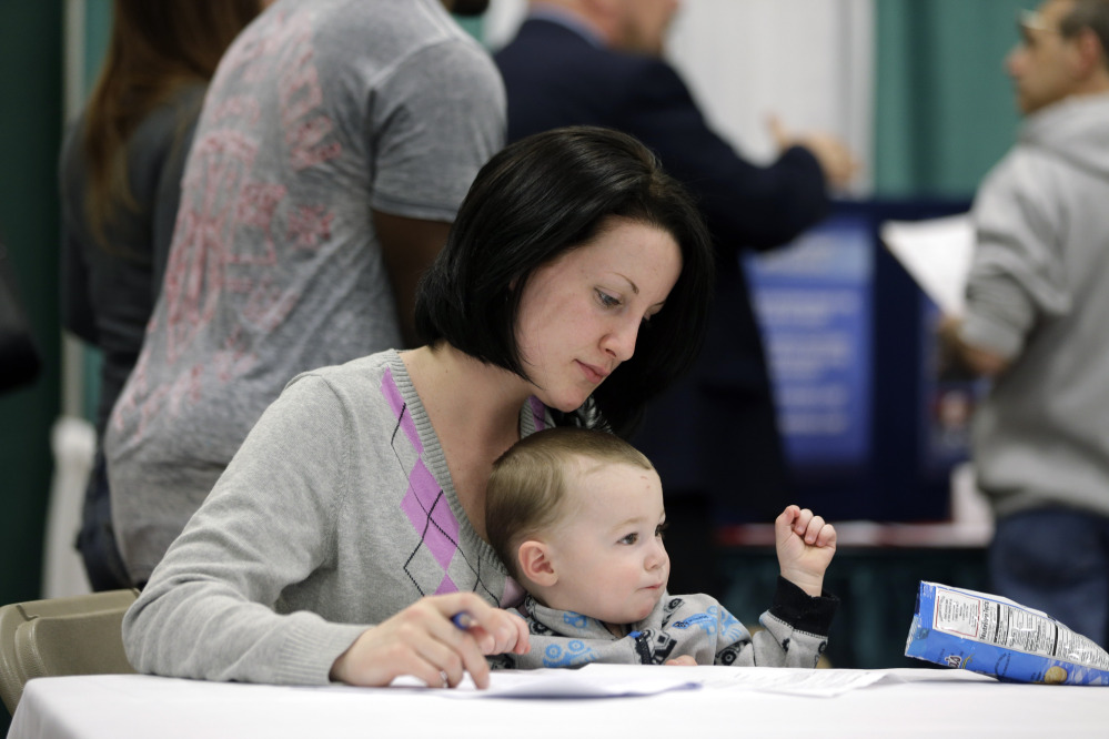 Sarah Keegan of Windham, N.Y., with her son Kevin, fills out paperwork during a job fair recently at Columbia-Greene Community College in Hudson, N.Y.