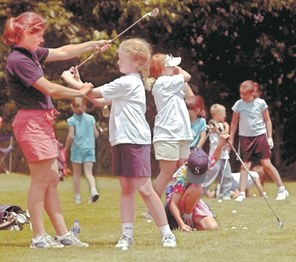 Seven-time Maine women's amateur champion Abby Spector instructs Maya Brown, 9, of Waterville during a clinic sponsored by Hardy Girls Healthy Women at Natanis Golf Course on Monday. The clinic and an accompanying 18-hole tournament were designed to encourage young girls to take up the game of golf.