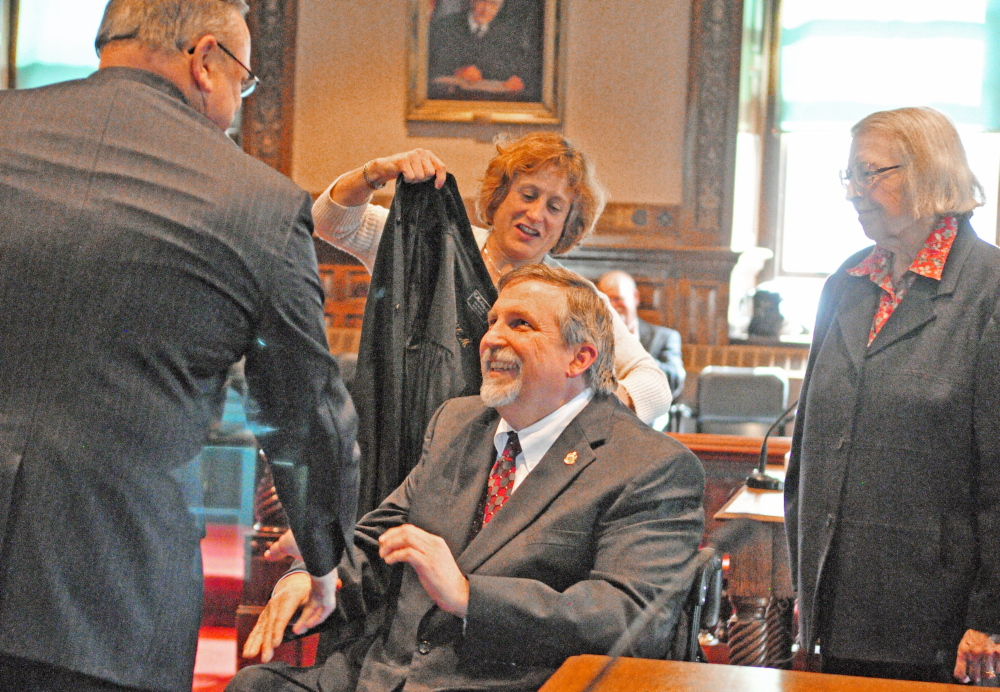 ROBING CEREMONY: After swearing him in, Gov. Paul LePage, left, shakes hands with new district court judge William J. Schneider during a swearing in ceremony at Kennebec County Superior Court in Augusta. His wife, Barbara Schneider, top and mother, Phyllis Schneider, stand behind him to put his robe on him. William Schneider served as attorney general from 2011-2013, LePage's first two years in office.