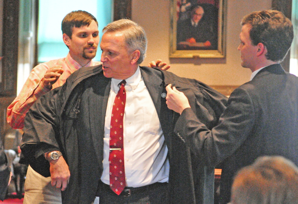 ROBING CEREMONY: Newly sworn in Superior Court Justice Robert Mullen, of Waterville, center, is enrobed by sons Sam Mullen, left, and Matthew Mullen during a swearing in ceremony on at Kennebec County Superior Court in Augusta. Mullen moved from being district court judge to superior court justice.