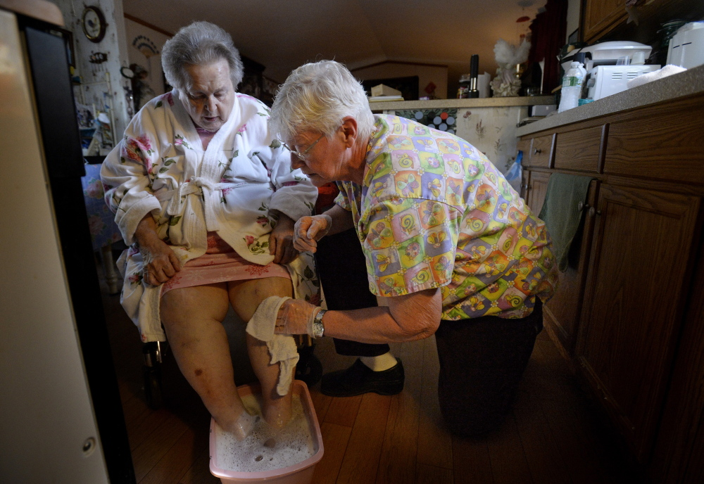 HELP AT HOME: Mildred Rood, 85, at left, is able to stay in her Windsor home thanks in part to the personal care services she receives from Nancy Boily, seen here washing her client's feet and legs with warm water in order to ease their pain and numbness. Compensation for Maine's home care workers hasn't kept up with the increasing demand for their services.