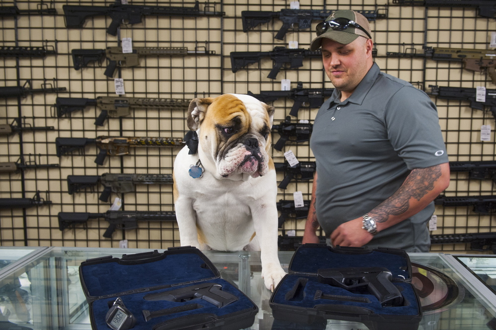 Engage Armaments owner Andy Raymond is shown Thursday at his store in Rockville, Md., with his dog Brutus. He backed away from plans to sell smart guns after getting threats.
