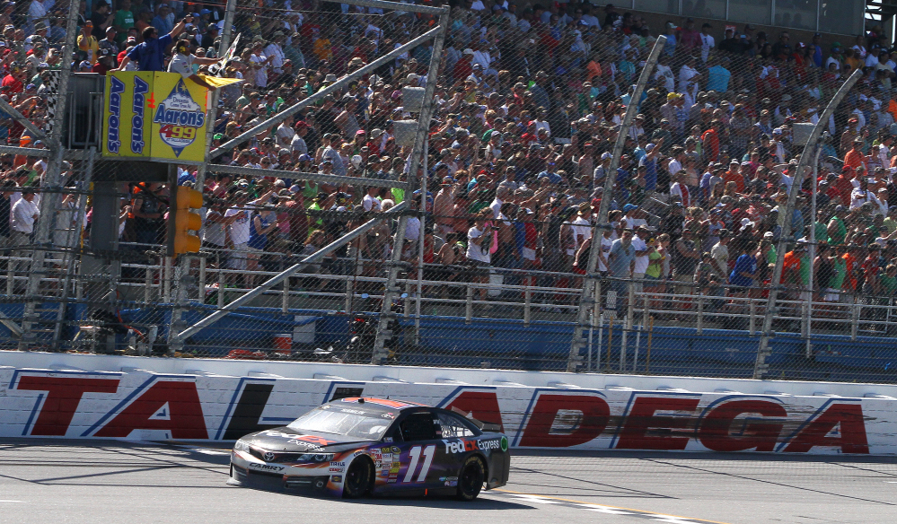 Denny Hamlin (11) takes the checkered flag under caution during the NASCAR Aaron's 499 Sprint Cup series auto race at Talladega Superspeedway on Sunday in Talladega, Ala.