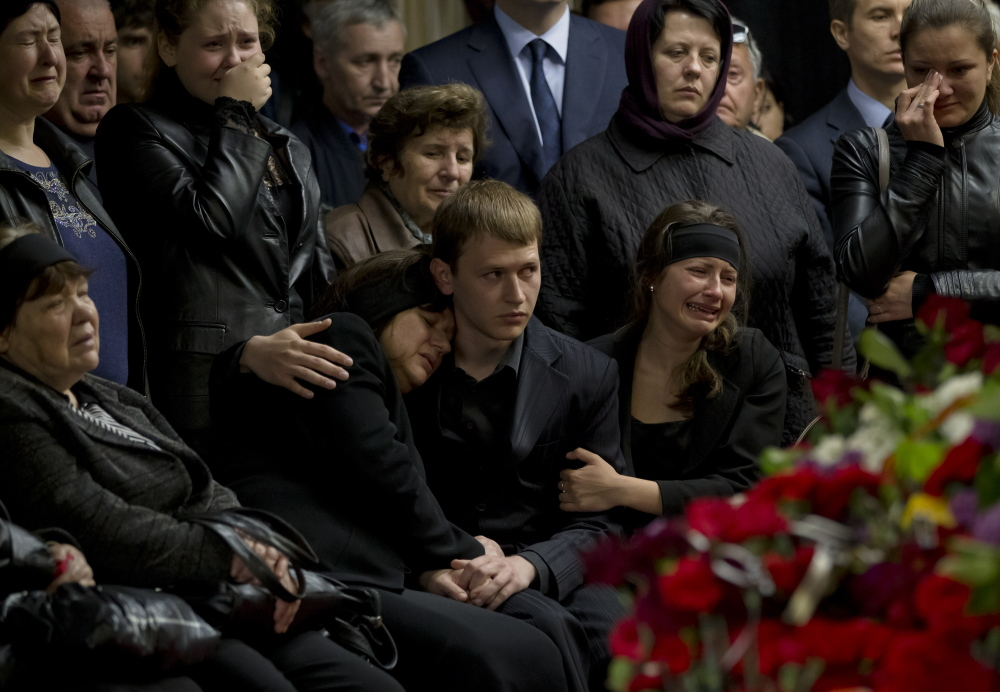 """Mourners cry next the coffin of regional parliament member Vyacheslav Markin in Odessa, Ukraine, on Monday. Markin, who was known for speaking out against the government in Kiev, was buried Monday while about 300 pro-Russian supporters shouted """"Hero, hero!"""" Markin died Sunday from burns sustained in Friday's fire."""