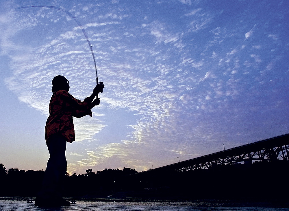 DAWN'S EARLY LIGHT: In this photo taken in July 2006, a fisherman gets up before dawn to cast into the Kennebec River from the floating dock in Augusta Waterfront Park. Even at 5:22 a.m., there were several fishermen on the shore and more in boats going after stripers.