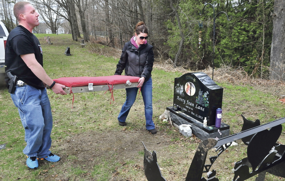 RETURN: Kennebec County sheriff's Deputy Jacob Pierce and Tabitha Souzer on Tuesday return a cushion to the bench that was thrown down an embankment near the grave site of Souzer's daughter, Avery Lane, in the Friends Cemetery in Fairfield.