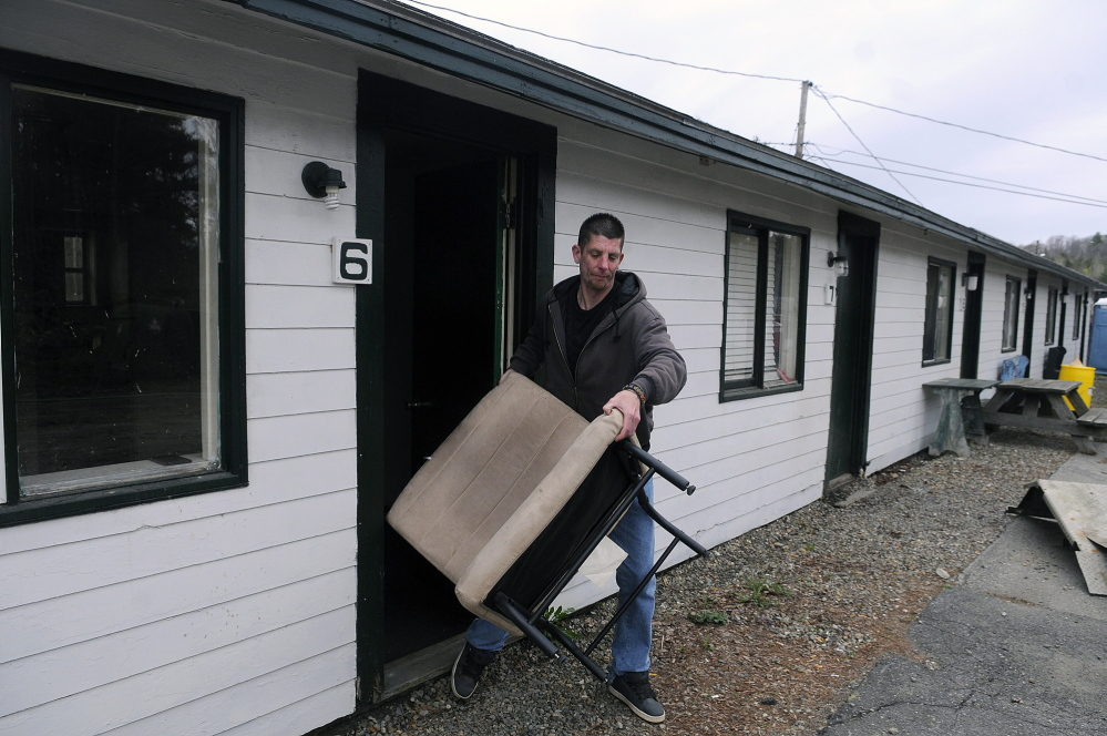 MOVING: Mike Johnson removes his belongings Tuesday from his former room at the Country Village Motel and Apartments in Augusta. The complex was closed after a sewer pipe broke.