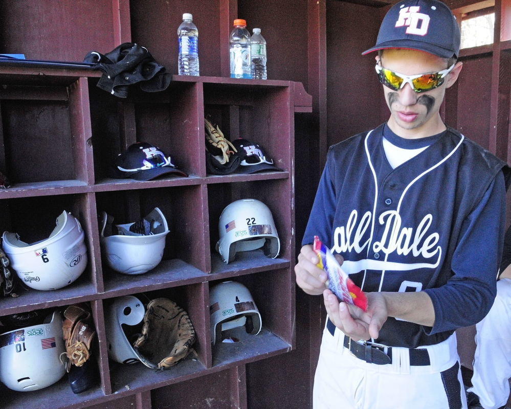 HARD HABIT TO BREAK: Hall-Dale outfielder Tyler Dubois grabs a handful of sunflower seeds before the start of a game Wednesday in Monmouth. The seeds, made in many different flavors, seem to be the snack of choice for players these days.