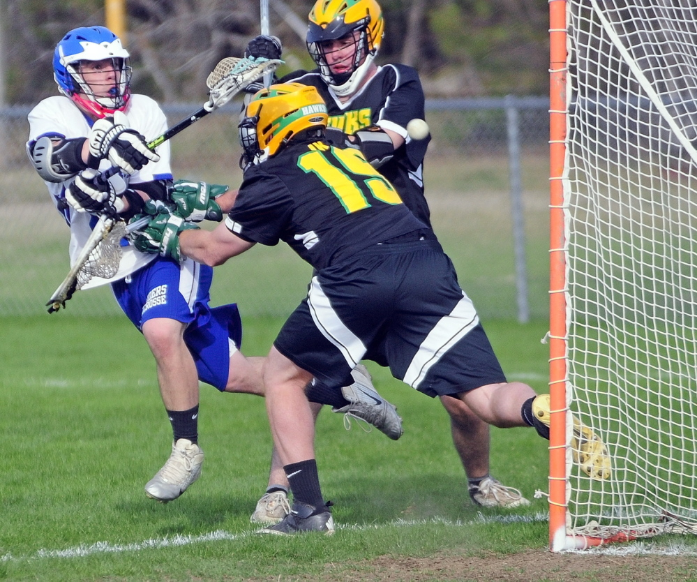 Oak Hill's Matt Gilbert, left, shoots and misses as Maranacook-WInthrop keeper Zachary Bessette pushes him back during a game on Thursday May 8, 2014 at Oak Hill High in Wales.