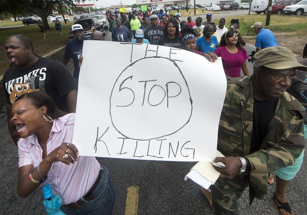 Protesters carry signs outside the Hearne, Texas, police department Thursday following the shooting death of 93-year-old Pearlie Golden by Officer Stephen Stem.