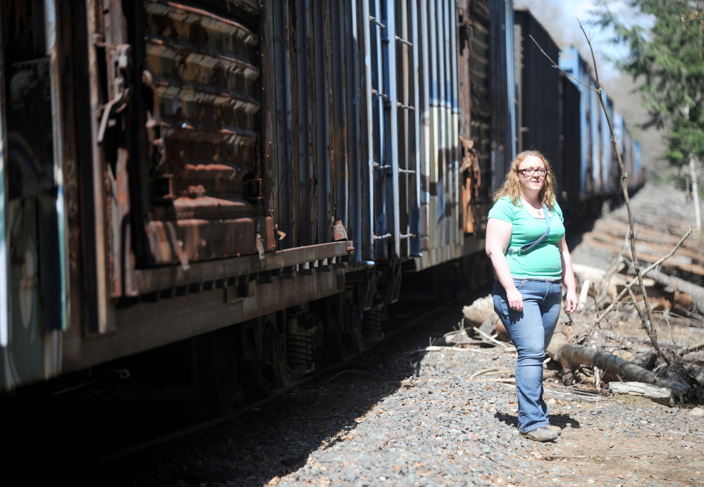 NEGLECTED: Miriam Easton stands by a neglected train on tracks that runs through her family's property on Fairfield Street in Oakland on Thursday.