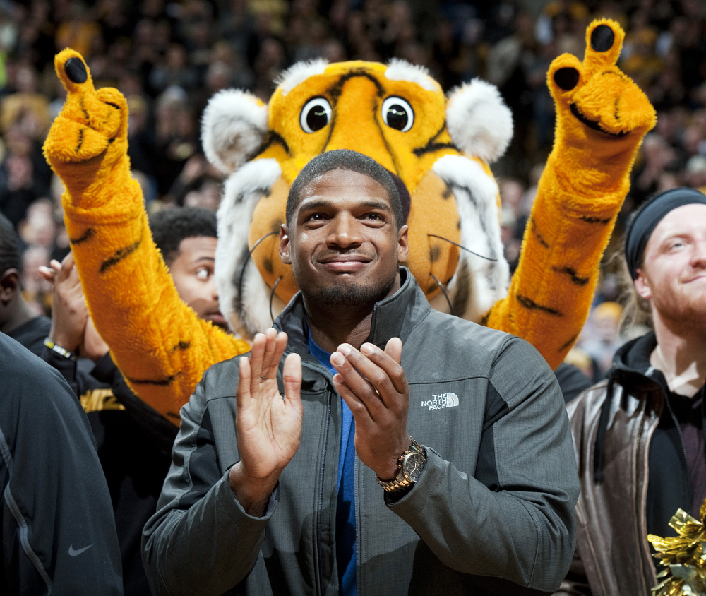 In this Feb. 15, 2014, file photo, Missouri's All-American defensive end Michael Sam claps during the Cotton Bowl trophy presentation at halftime of an NCAA college basketball game between Missouri and Tennessee in Columbia, Mo.