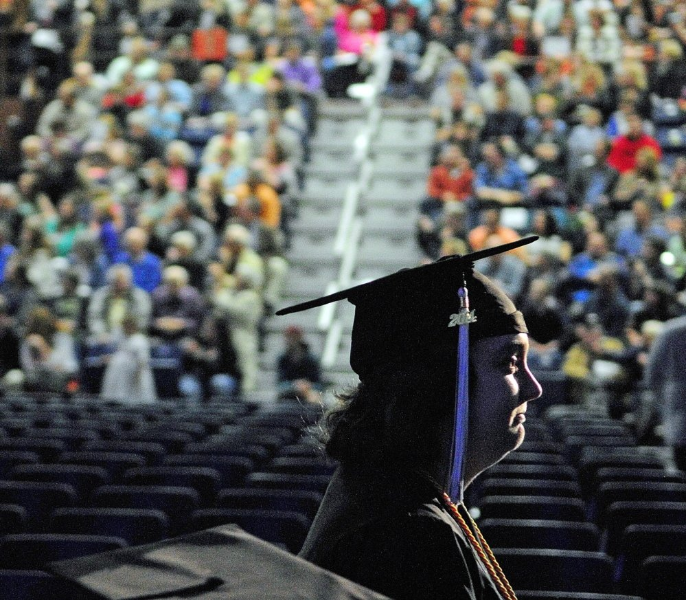 DIPLOMA-BOUND: A graduate marches in front of a large crowd during the University of Maine at Augusta graduation ceremony Saturday at the Augusta Civic Center.