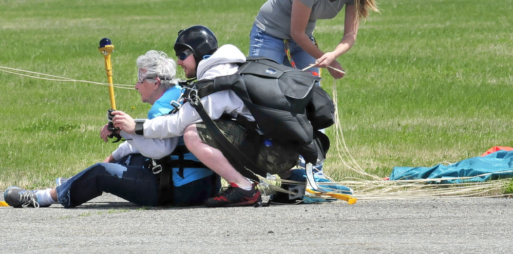TERRA FIRMA: Marjorie Bell, 80, catches her breath seconds after landing with instructor Matt Riendeau after tandem skydiving at LaFleur Airport in Waterville on Sunday, May 11, 2014.