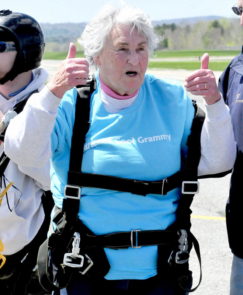 YOUNG AT HEART: Marjorie Bell, who turned 80 on Saturday, gives the thumbs-up sign to family members after she successfully skydived in tandem at LaFleur Airport in Waterville on Mother's Day, Sunday, May 11, 2014.