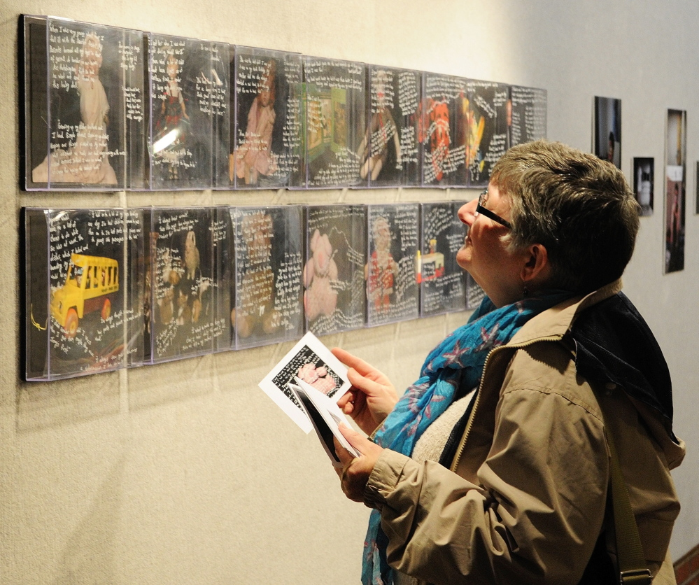 """Portraits: Donna Sellers, of Waterville, looks at """"Family Portrait: Toy Series"""" by Heather Marlow at the opening for the Senior Art Show on Saturday May 10, 2014 in the Danforth Gallery at the University of Maine at Augusta."""