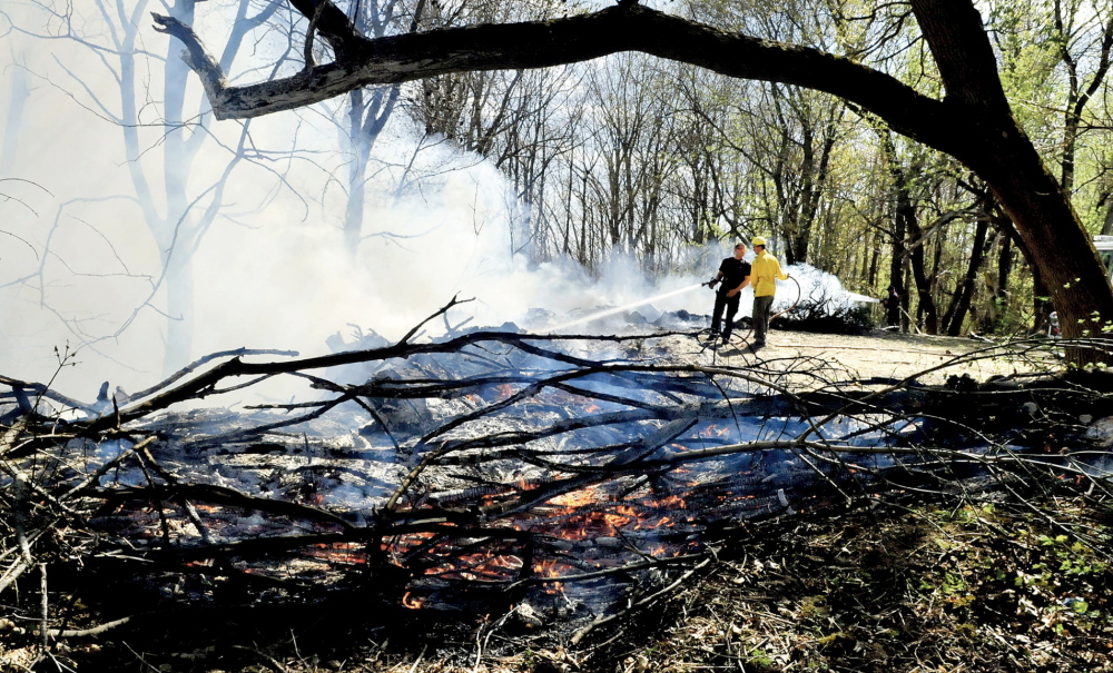 HOT FIRE: Waterville firefighters Pablo Passalacqua, left, and Dan Brown extinguish fire in a pile of brush near the woods at the rear of Pine Grove Cemetery on Monda.