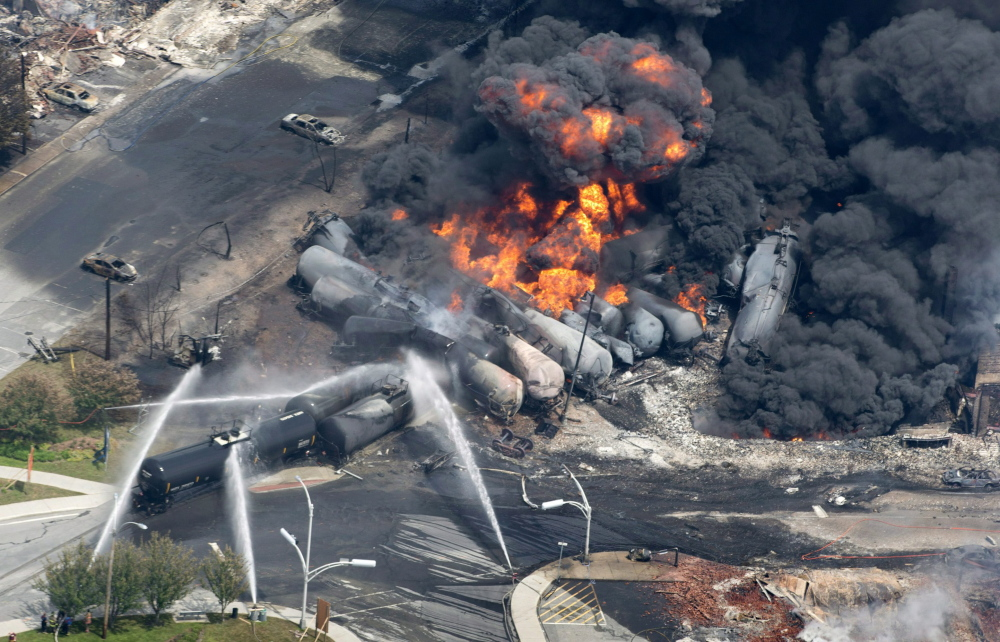 This July 6, 2013, file photo shows smoke rising from railway cars that were carrying crude oil after derailing in downtown Lac-Megantic, Quebec. The tragedy occurred when a runaway train carrying 72 carloads of crude oil derailed, hurtled down an incline and slammed into downtown Lac-Megantic. Several train cars exploded, 40 buildings were leveled and 47 people were killed.