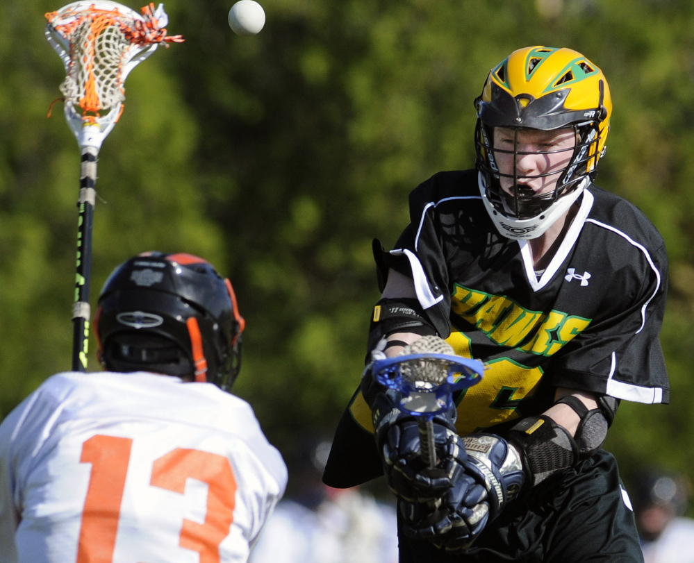 Staff photo by Andy Molloy Maranacook-Winthrop's Logan Emery, right, takes a shot over Gardiner's Chase Begin during a lacrosse match-up Monday in Gardiner.