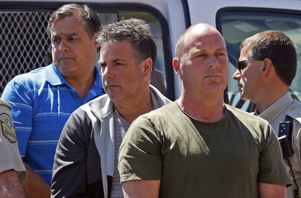 Thomas Harding, right, Jean Demaitre, center, and Richard Labrie are escorted by police officers as they arrive at the courthouse in Lac-Megantic, Quebec, on Tuesday.