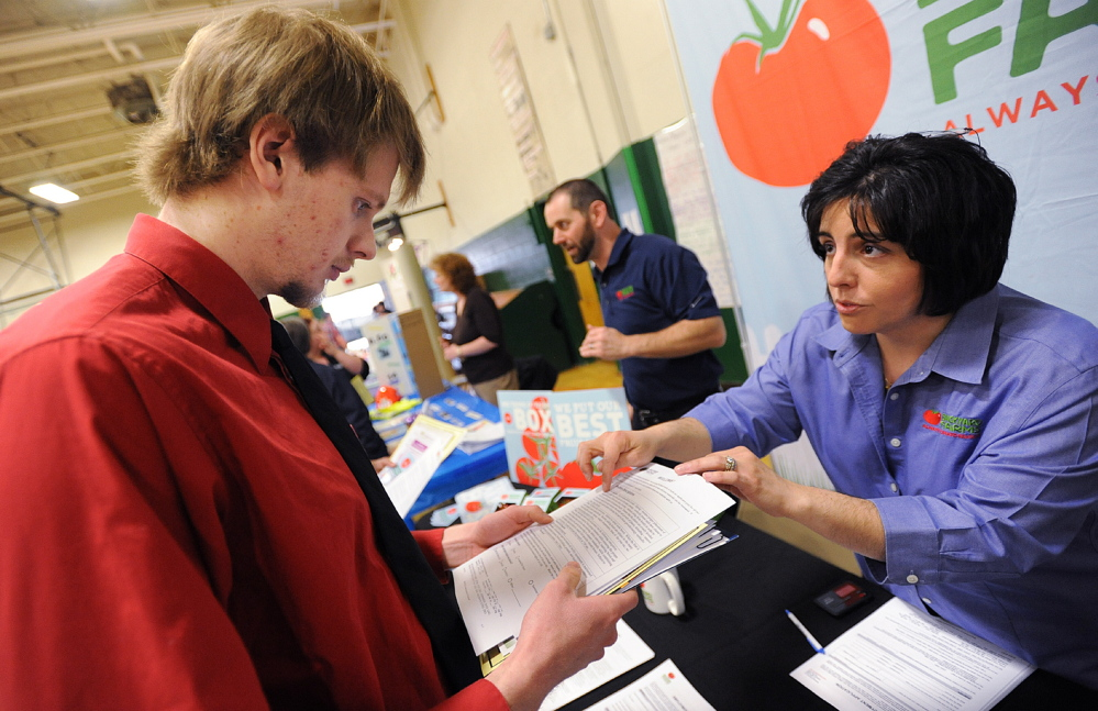 JOB SEEKING: United Technologies Fire and Safety employee John Faloon of Hartland talks with Backyard Farms director of human resources Dawn Palmer during the job fair in Pittsfield on Wednesday. Fallon will lose his job when UTC closes next spring.