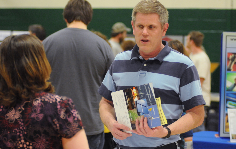 MAKING CONNECTIONS: United Technologies employee Jeffrey Carmichael of Pittsfield talks with senior tax examiner Maria French during the job fair in Pittsfield on Wednesday. Carmichael will lose his job when UTC closes next spring.