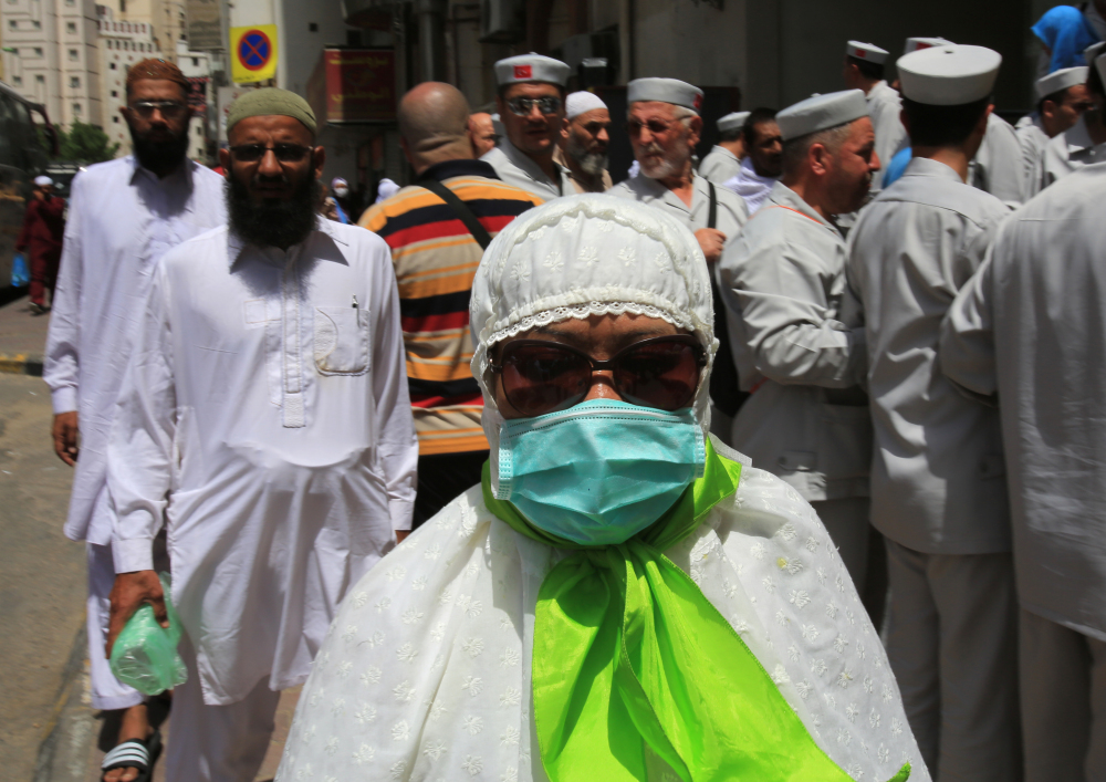A Muslim pilgrim wears a surgical mask to help prevent infection from a respiratory virus known as the Middle East Respiratory Syndrome in the holy city of Mecca, Saudi Arabia, Tuesday. Saudi health authorities reported another five deaths Tuesday from MERS that has sickened hundreds and killed over 150 people.