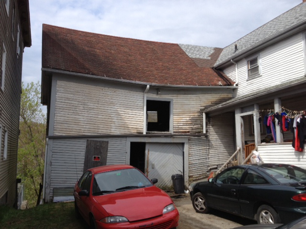Displaced: Damage from a Tuesday night fire that in a Northern Avenue barn, seen here Wednesday, wasn't very visible from the streeet, but forced two families living next door to evacuate.