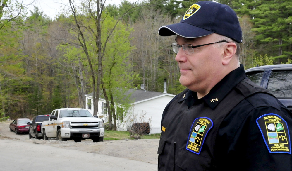 POLICE PRESENCE: Skowhegan Police Chief Ted Blais speaks outside a North School Street residence as police from several agencies searched the home on Wednesday.