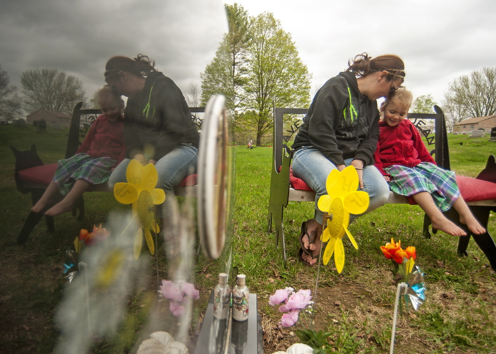 TOGETHER: Riley Souzer, 2, cuddles with her mother Tabitha, at the grave site of her daughter, Avery Jean Lane, at North Fairfield Friends Meeting House cemetery on Thursday. Lane's grave site was recently vandalized.