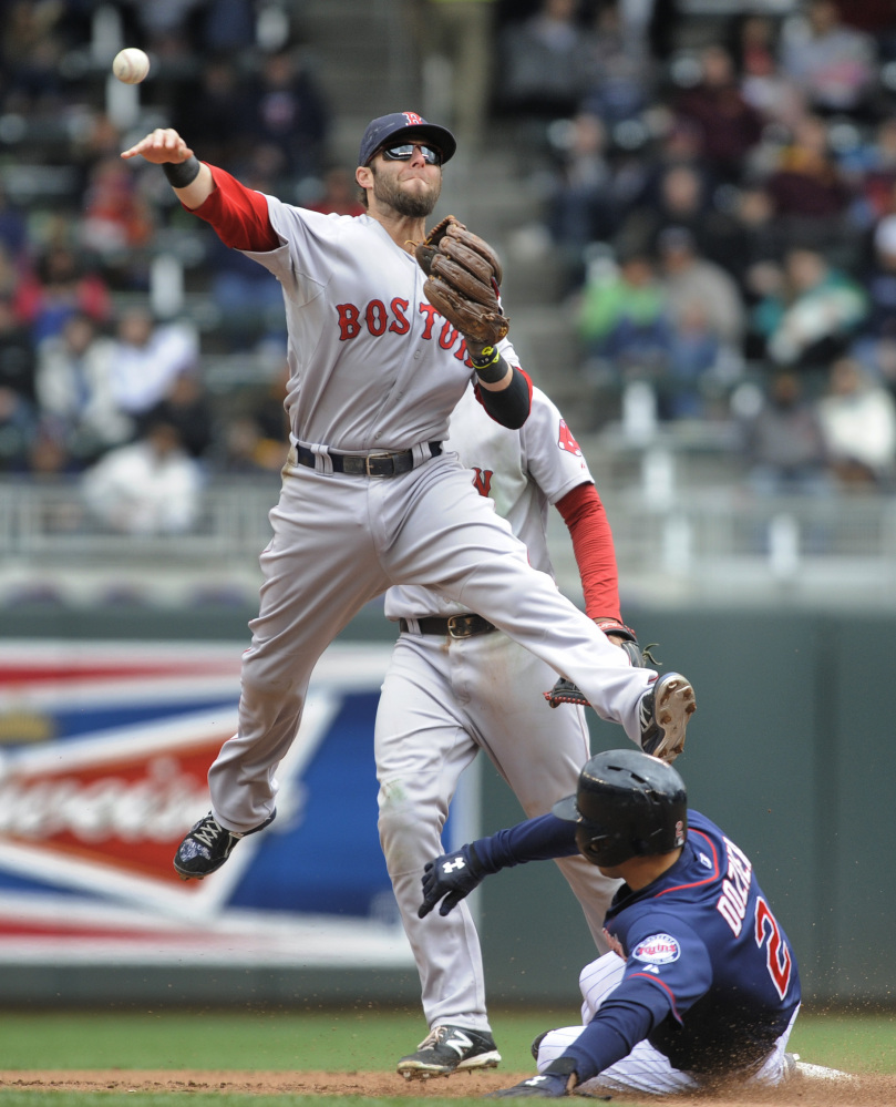 Boston Red Sox second baseman Dustin Pedroia sails over the Minnesota Twins second baseman Brian Dozier after getting the force at second in the fourth inning Thursday.
