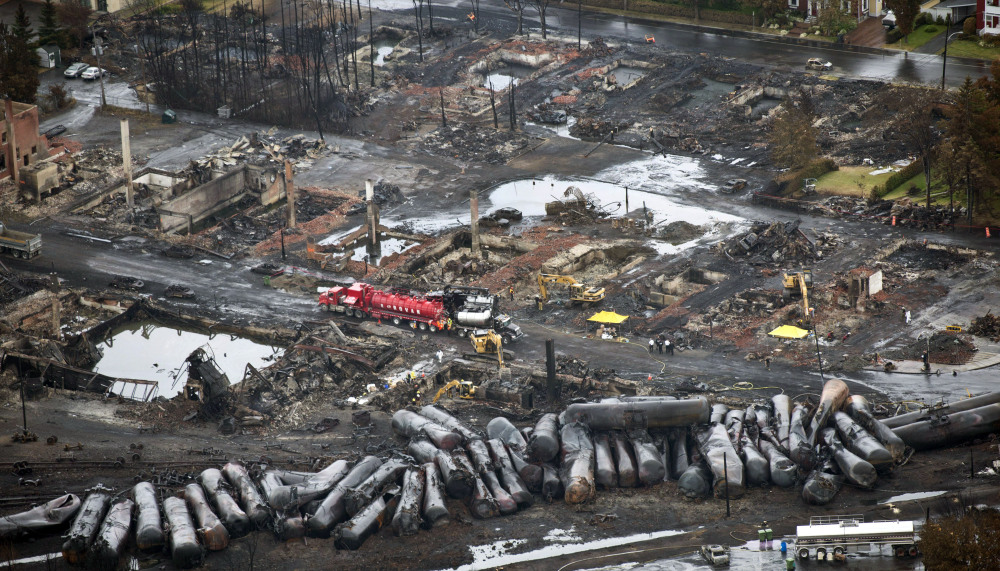 Workers comb through debris on July 9, 2013, after an unmanned train with 72 railway cars carrying crude oil derailed, causing explosions in Lac-Megantic, Quebec. The railroad hopes to make safety improvements that would allow the resumption of oil shipments by 2016.