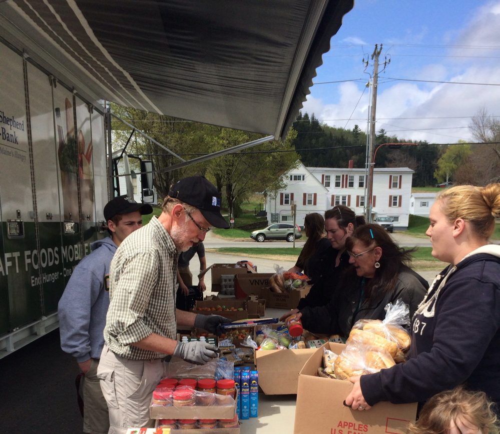 HELPING OUT: Volunteer Doug Boyce, left, helps Christie Cromwell, right foreground, and June Cromwell, background, fill boxes with food outside the Bingham Area Health Center on Friday. The health center partnered with the Good Shepherd Food Bank in Auburn to bring a mobile food pantry to Somerset County.