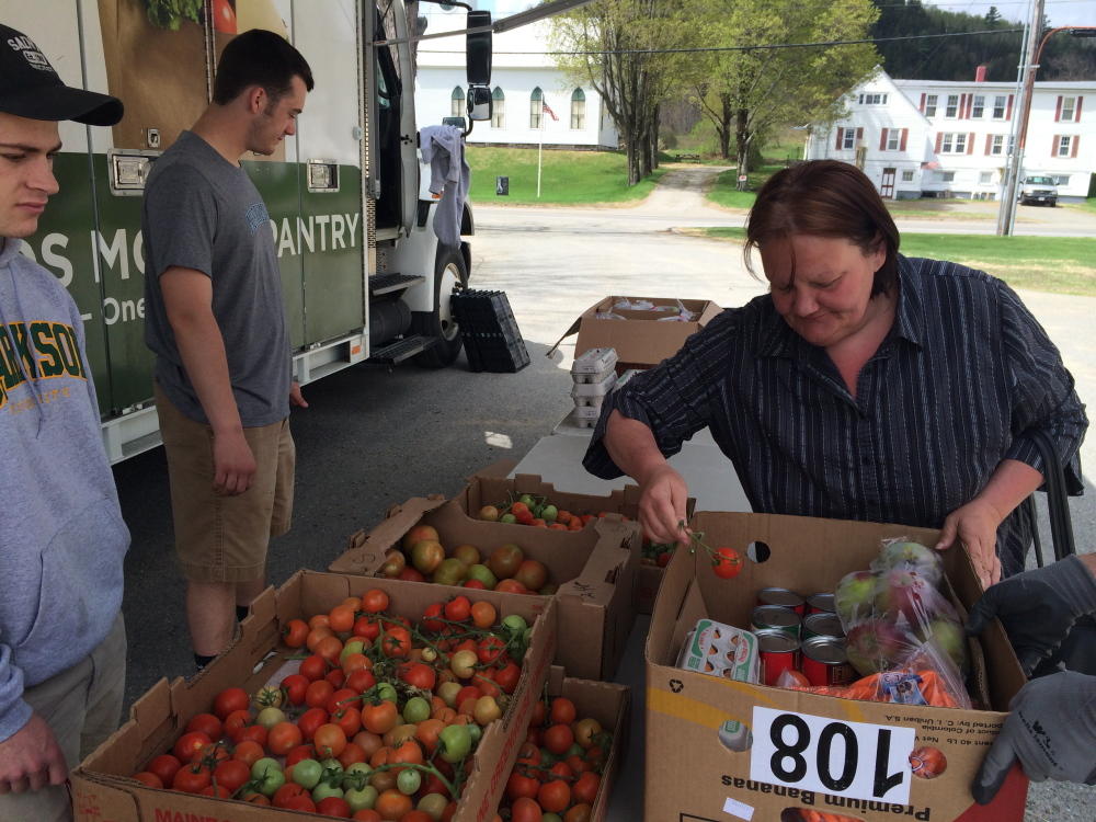 FRESH FOOD: Julie Bradley, 51, of Moscow, picks up some fresh tomatoes from the Good Shepherd Food Bank Mobile Food Pantry on Friday in Bingham, while volunteer Calvin Stewart, 18, watches.