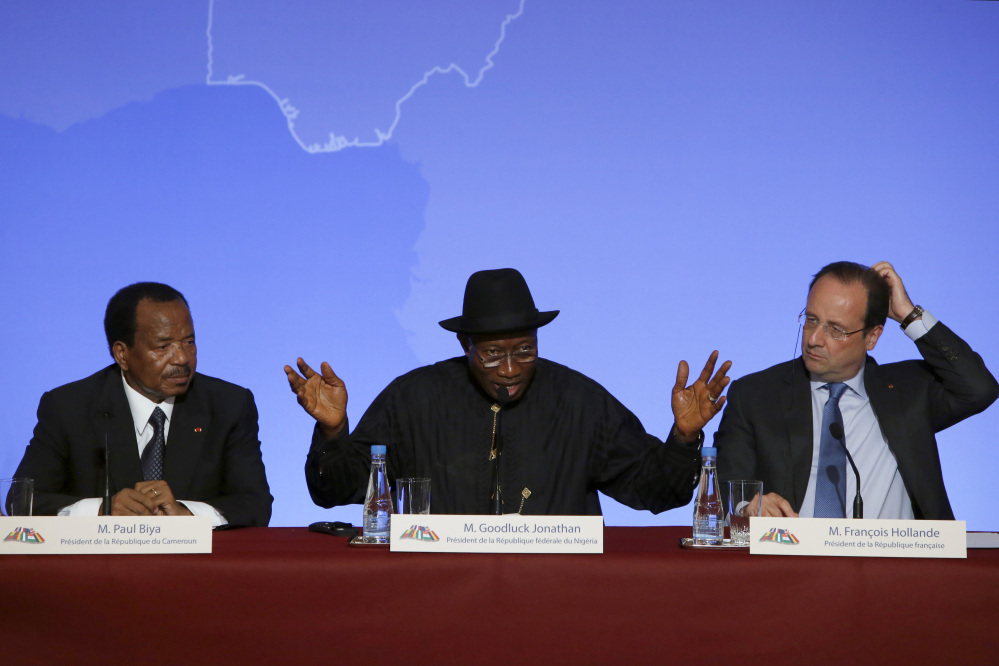 """Nigeria President Goodluck Jonathan, center, answers reporters' questions. He is flanked by Cameroon President Paul Biya, left, and French President Francois Hollande during a news conference ending the """"Paris Summit for Security in Nigeria"""