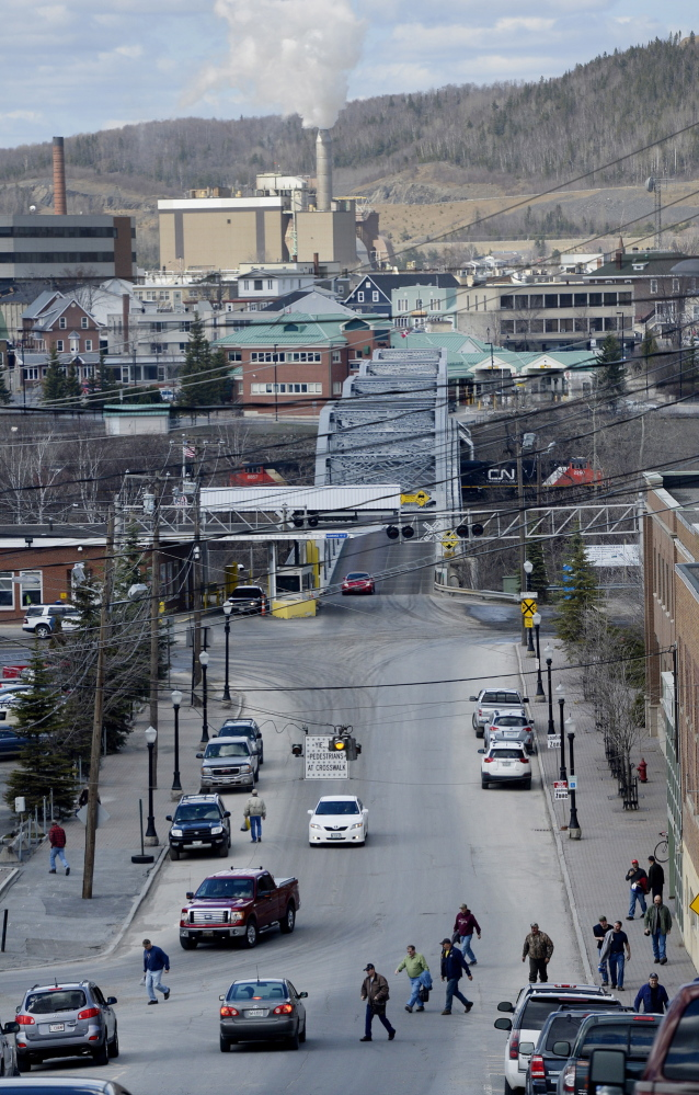 Workers file onto Bridge Avenue after a shift at the Twin Rivers Paper Co. mill in Madawaska. Edmundston, Canada. the neighboring community, can be seen across the bridge. Although Madawaska's median income is only about $33,500 a year, most older men have made a decent living working union jobs at the mill.