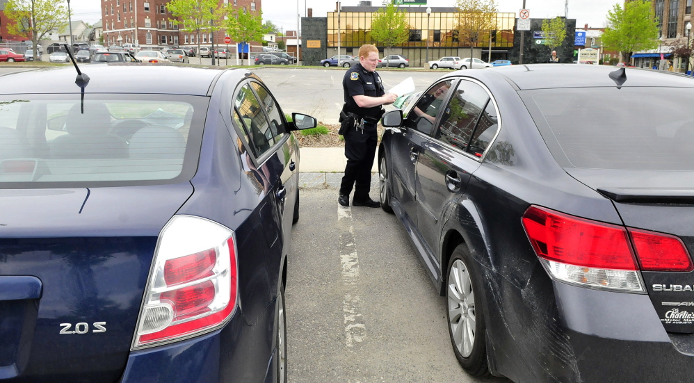 WARNING: Waterville police officer Robert Bouley places a warning and a map for new parking regulations Thursday in The Concourse on a car that was parked longer than the space's two-hour limit. Behind Bouley is the area where farmers market vendors set up every Thursday.