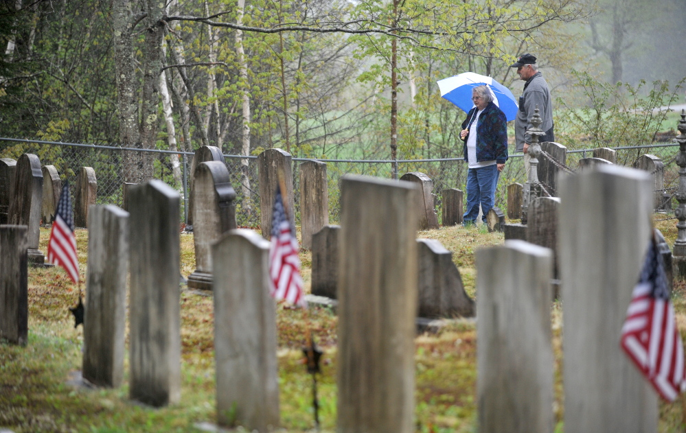 Communing with the past: Elsie Bonney and her husband, Larry Bonney, of Bethel, browse among the various headstones Saturday at Frederic Cemetery in Starks. The Maine Old Cemetery Association, which works to preserve old cemeteries, held its annual spring meeting in Starks.