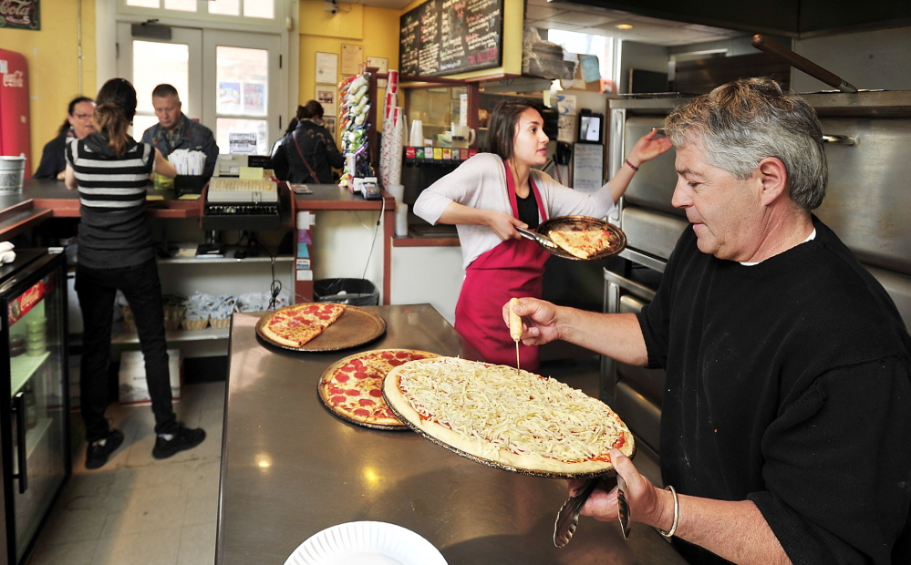 Owner John Bergeron helps employees at Bill's Pizza, which received a 100-pie order from the Nova Star, above, this month.