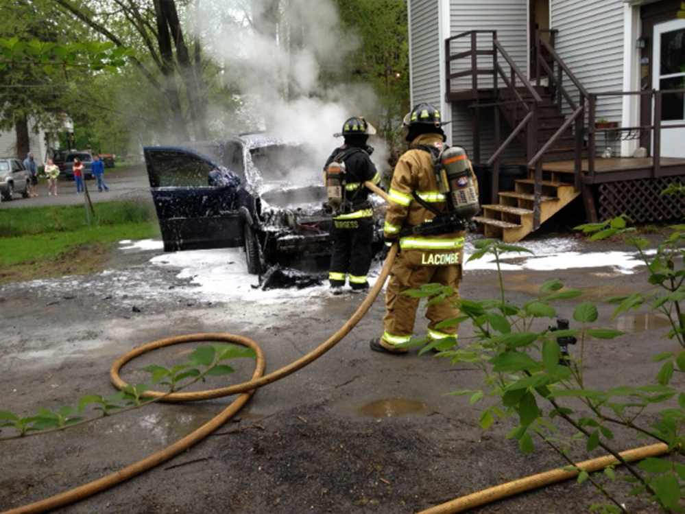 Fire response: Winslow firefighters work to put out a fire that destroyed a Buick Rendezvous sport-utility parked behind an apartment building at 90 Clinton Ave. Monday morning.