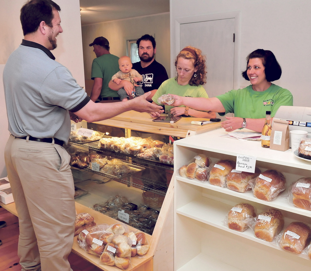 FOOD: Sandy Wiles, right, hands fresh baked pastry to Belgrade Lakes Postmaster Dexter Bridges at the new Pine Bluff Farms Store on Route 27 in Rome on Tuesday. Looking on is Steve Decker holding, Jacob, and manager Ashley Decker.