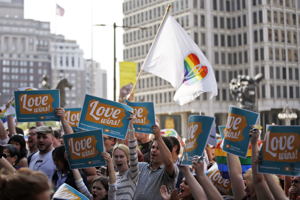 People hold up signs and cheer during a rally at City Hall, Tuesday, May 20, 2014, in Philadelphia. Pennsylvania's ban on gay marriage was overturned by a federal judge Tuesday.