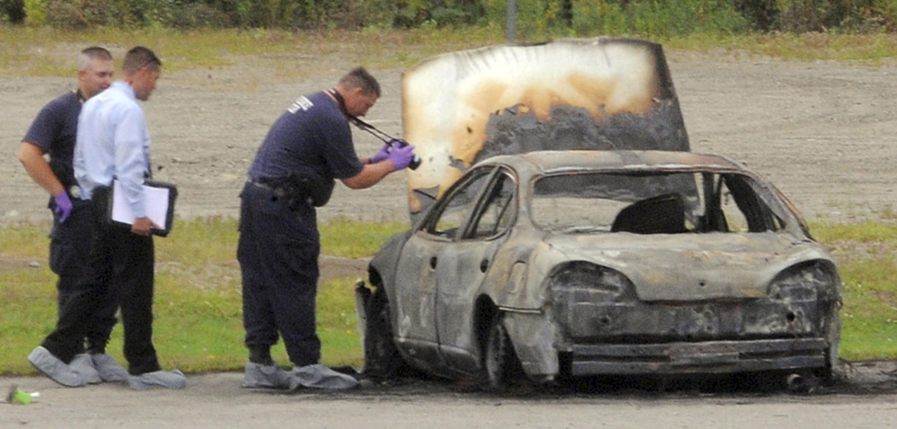 Police investigate a burned vehicle in Bangor on Aug. 13, 2012. The bodies of three Maine residents were found inside the car. Two men are on trial for the killings.
